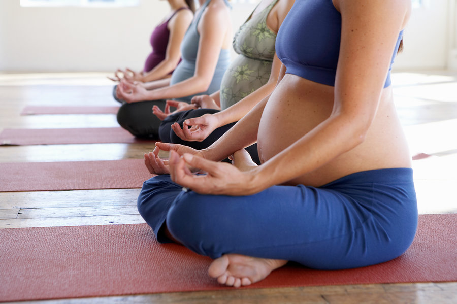 Pregnant women in a yoga class sitting in a position of meditation