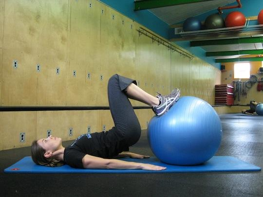Personal Trainer, Tatum Rebel demonstrates hamstring curl with ball